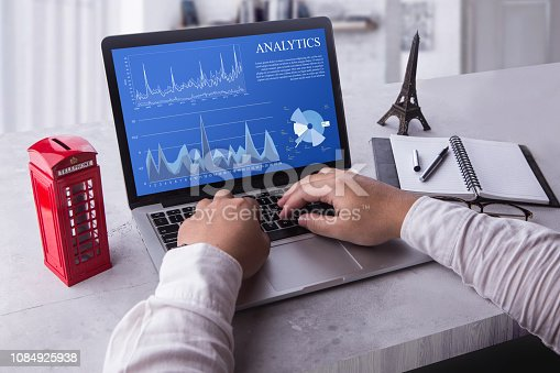 istock Top view of a businessman laptop computer with analytics data concept on screen. Working with financial graphs charts, using business software for data analysis and project management concept 1084925938