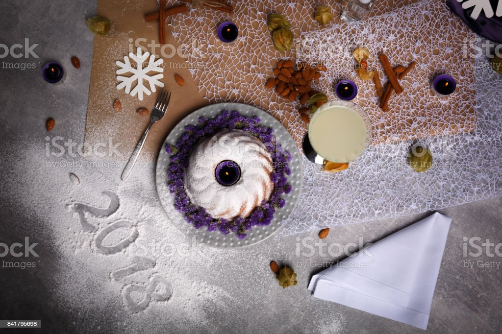 Top view of a cake next to a 2018 new year sign. Christmas dinner on a table background. Christmas composition concept. stock photo