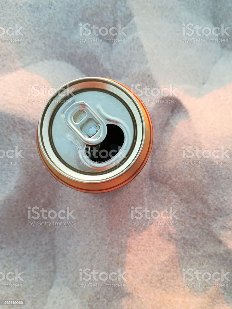 A top view of a can of beer resting on top of beach sand. This image can be used to represent drinking alcohol on the beach or outdoor recreation. - Royalty-free Alcohol Stock Photo