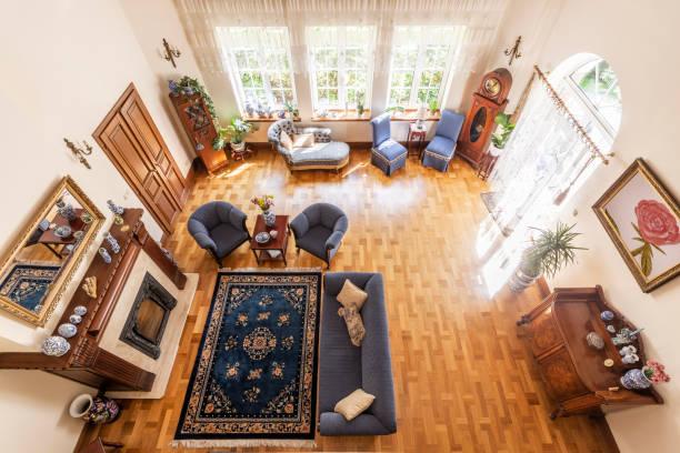 draufsicht auf eine klassische wohnzimmer interieur mit einen blauen teppich, sofa, sessel, große fenster, kamin und parkett. echtes foto - teppich englisch stock-fotos und bilder