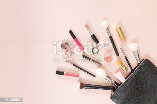 Top view of a cosmetic bag with make up products on a pastel pink background, flat lay