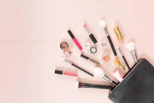 vue de dessus d'un sac cosmétique avec composent des produits sur un pastel fond rose, plat poser - maquillage et cosmétiques photos et images de collection