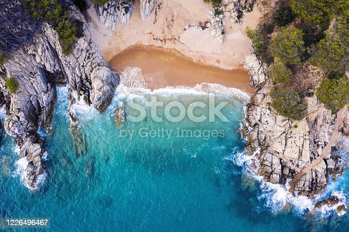 top view of a cove of turquoise waters surrounded with rock sea cliffs covered with trees and vegetation, concept of adventure lifestyle and summer luxury holidays in the wilderness