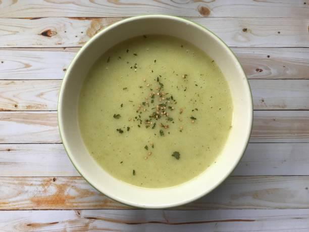 bovenaanzicht van een crème soep van courgette en groenten met sesam en peterselie in een witte kom in een lichte houten achtergrond - mergpompoen stockfoto's en -beelden