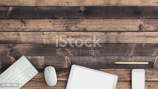 Knolling, top view of a half empty desk, with objects at the bottom,tablet, smartphone, keyboard. Top part of the photo is empty and free for additional elements. Copy space. Table top is made out of dark vintage wood. Horizontal wide letterbox composition