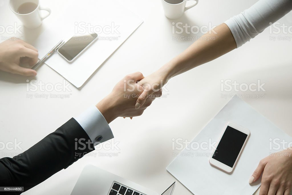 Top view of a handshake between man and woman stock photo