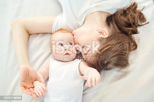 istock Top view of a happy mother kissing a baby lying on a bed 1003318856