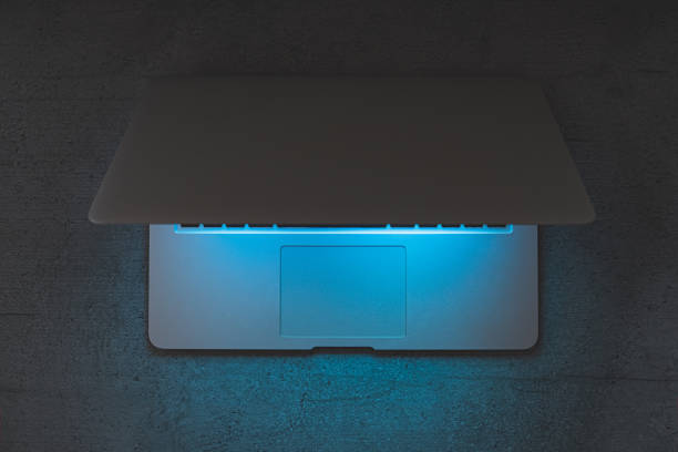 Top view of a laptop on a dark table, glowing blue screen. stock photo