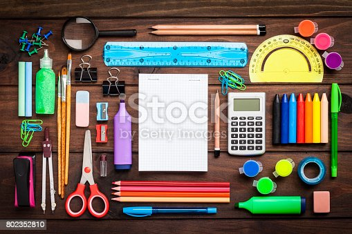 Top view of a large group of multi colored school or office supplies shot on rustic dark wooden table. A blank note pad is at the center of the composition with useful copy space ready for text and/or logo. DSRL studio photo taken with Canon EOS 5D Mk II and Canon EF 100mm f/2.8L Macro IS USM