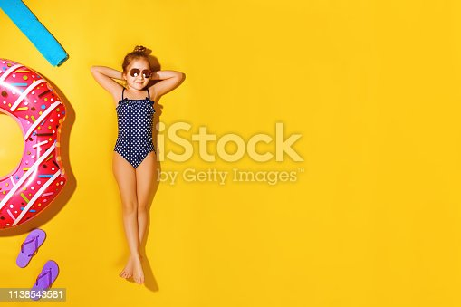 Top view of a little girl in sunglasses lying on the floor with slippers, a towel and an inflatable circle donut on the side. A child in a bathing suit resting on a yellow background.