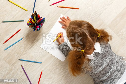 Top view of a little girl lying and painting on the floor in her room at home.