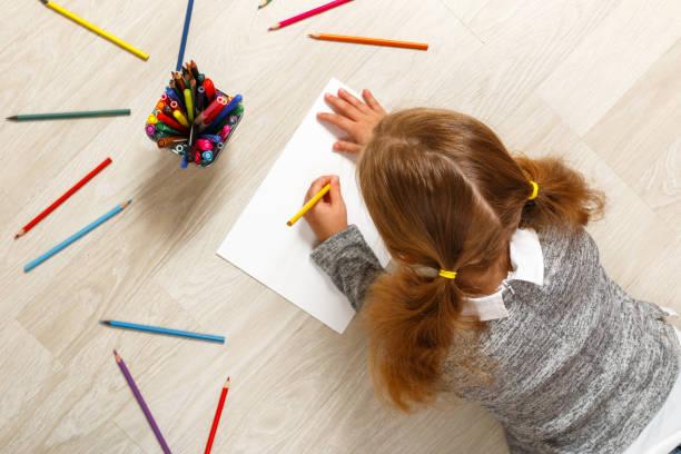 vista superior de una niña acostada y pintando en el suelo de su habitación en casa. - dibujar fotografías e imágenes de stock