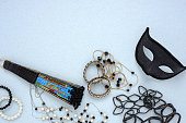 Top view of a lot of jewelry, costume jewelry, black masquerade mask and fan, on a blue background.