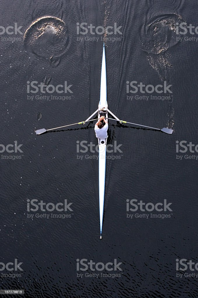 Top view of a man rowing his boat on dark water royalty-free stock photo