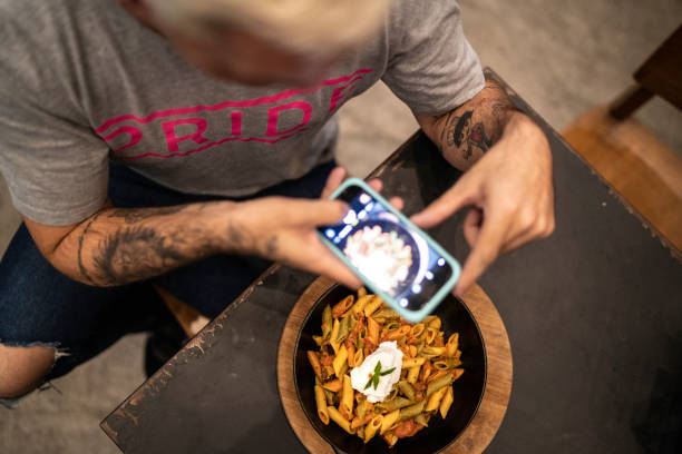 top view of a man taking picture of a pasta dish using cellphone - foodie stock photos and pictures