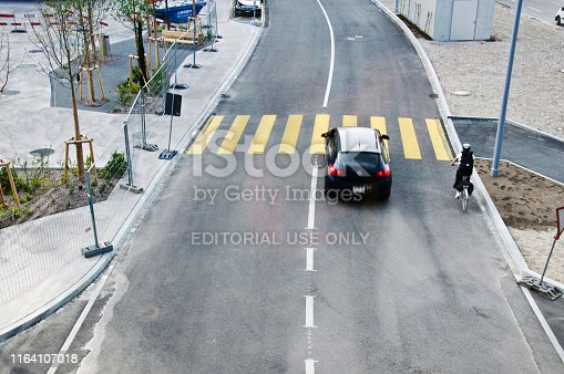 144334852 istock photo Top view of a motorway/street traffic. A swiss cyclist and a car go past a zebra crossing in Basel - Switzerland 1164107018