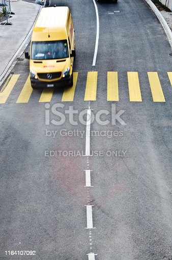 144334852 istock photo Top view of a motorway/street traffic. A swiss DHL courier motorist drive over a zebra crossing in Basel - Switzerland 1164107092