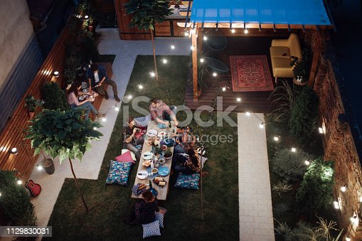 istock Top view of a Multi-ethnic friends enjoying dinner party at yard 1129830031