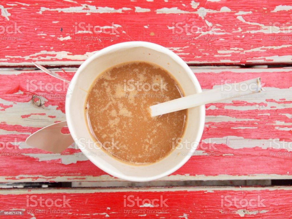 Top view of a paper cup of black coffee on red wooden table royalty-free stock photo