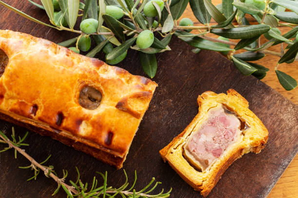 Top view of a pate en croute or pâté en croûte with rosemary twig and green olives on branch with leaves over a dark wooden cutting board and a used oak wood background. stock photo