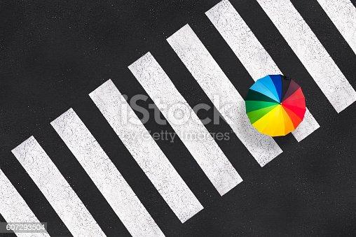 istock Top view of a rainbow umbrella on a pedestrian crosswalk 607293504