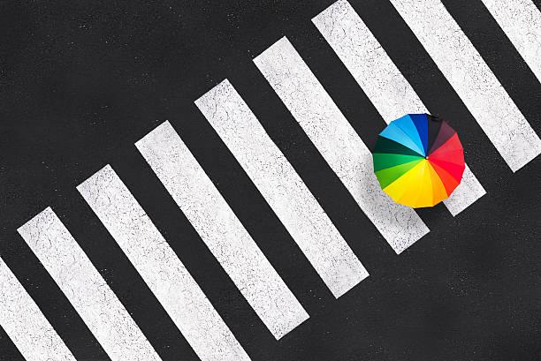 Top view of a rainbow umbrella on a pedestrian crosswalk - Photo