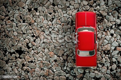 Top view of a red colored 1960 Chevrolet Nova toy model car on a country the road