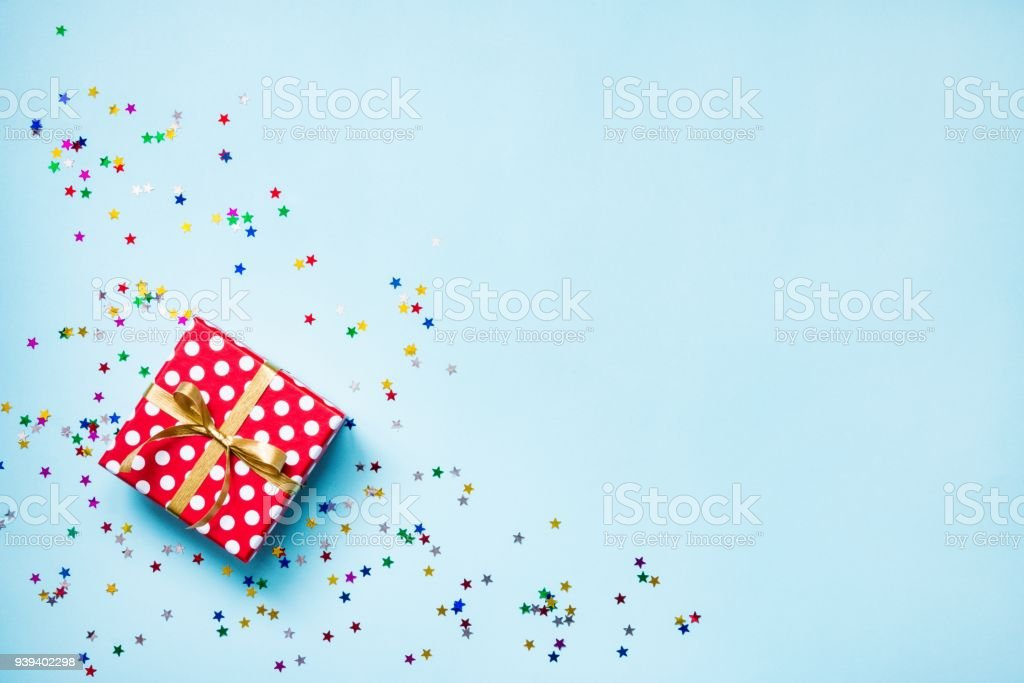 Top view of a red dotted gift box and scattered glittering star shaped confetti over blue background. Celebration concept. Copy space. stock photo