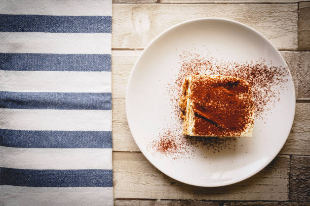 Top view of a slice of homemade tiramisu (traditional Italian dessert) on a white plate on a wooden board with a white and blue kitchen cloth. Top view of a slice of homemade tiramisu (traditional Italian dessert) on a white plate on a wooden board with a white and blue kitchen cloth. Landscape format. tiramisu stock pictures, royalty-free photos & images