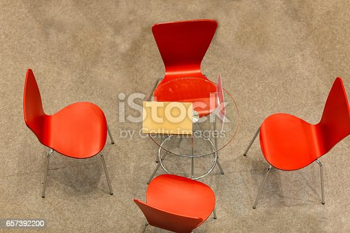 847512708 istock photo Top view of a small business meeting round table with four red chairs on floor copy space 657392200