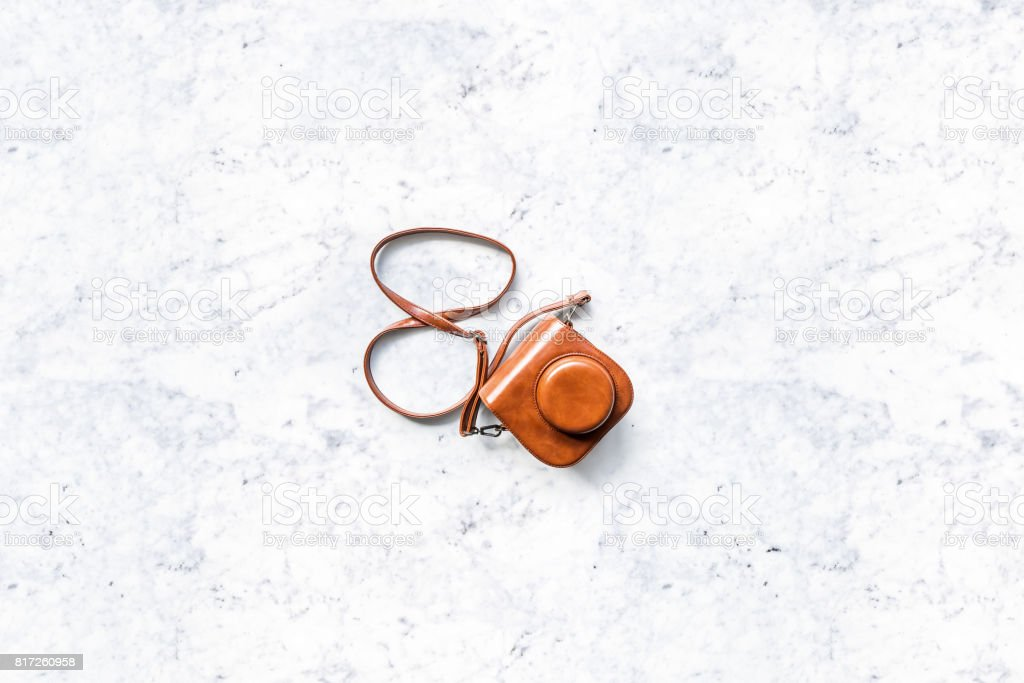 Top view of a small camera in a vintage brown leather case on a white marble table stock photo