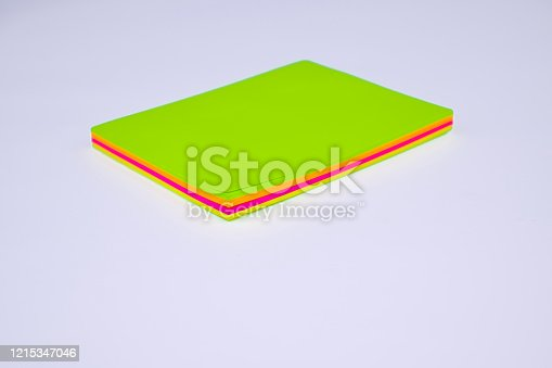 1090161334 istock photo Top view of a stack of different colored paper sticky notes on top of a white desk 1215347046