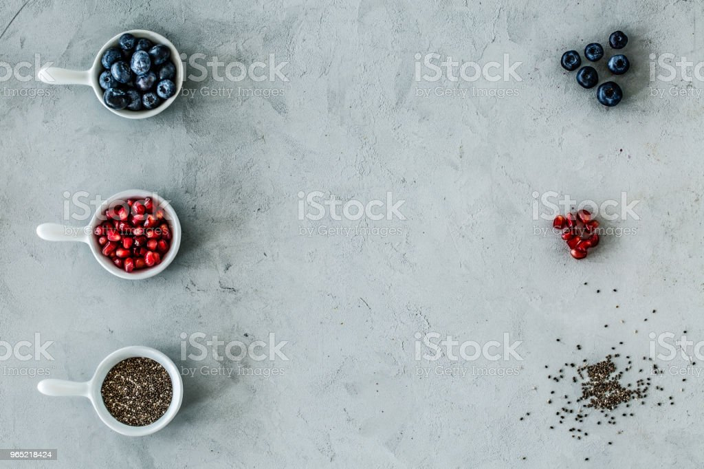 Top view of a symmetrical arrangement of blueberries, pomegranate and seeds on a gray table. royalty-free stock photo