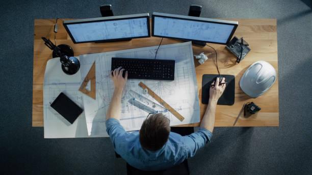 vista superior de un ingeniero técnico trabajando en sus planos, elaboración de planes, utilizando el ordenador de sobremesa. varios útiles artículos acostado sobre su mesa. - ingeniero fotografías e imágenes de stock