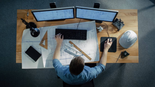 top view of a technical engineer working on his blueprints, drawing plans, using desktop computer. various useful items lying on his table. - engineer stock pictures, royalty-free photos & images