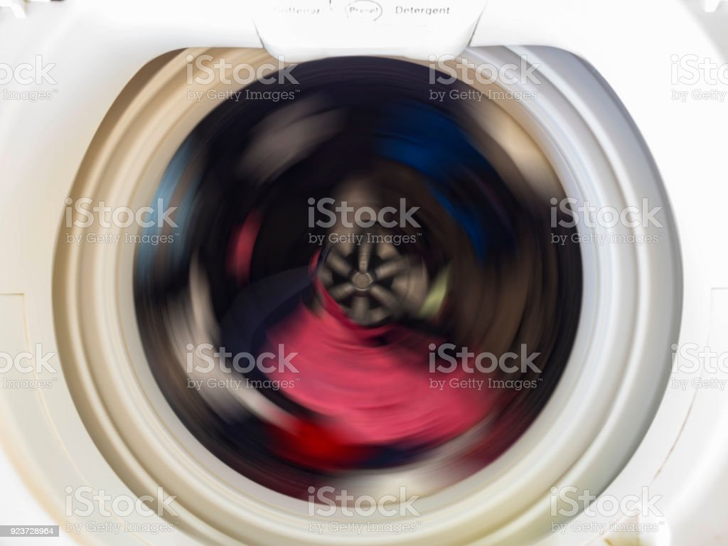 Top view of a washing machine drum during spinning clothes. Top loading washing machine washes laundry. stock photo