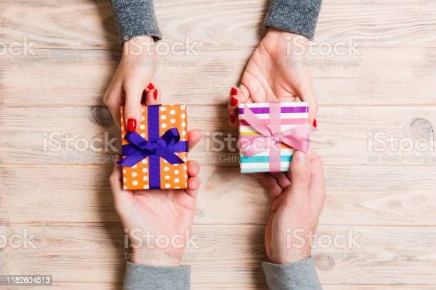 Top view of a woman and a man exchanging gifts on wooden background picture id1182604513?b=1&k=6&m=1182604513&s=612x612&h=apj63nvf7qayktbxru m9oshu6yn p1mv7roku1pops=