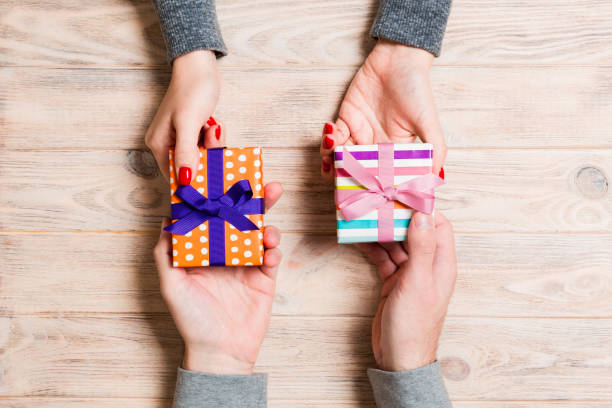 Top view of a woman and a man exchanging gifts on wooden background. Couple give presents to each other. Close up of making surprise for holiday concept stock photo
