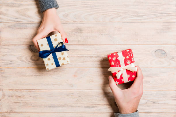 Top view of a woman and a man exchanging gifts on wooden background. Couple give presents to each other. Making surprise for holiday concept with copy space stock photo