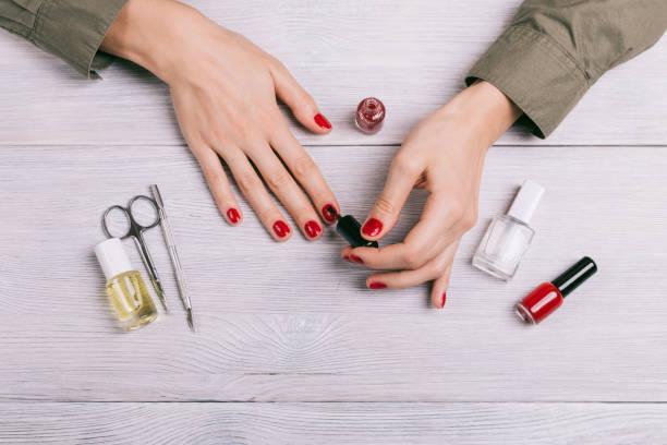 top view of a woman doing a manicure - nägel lackieren stock-fotos und bilder