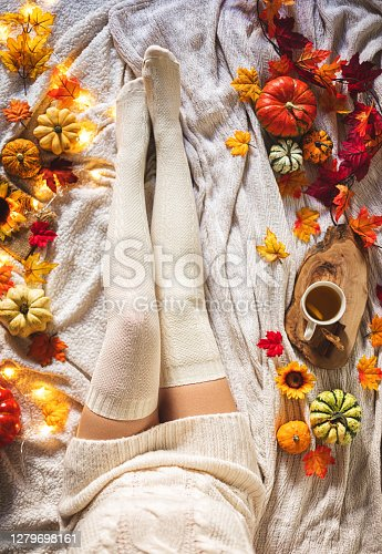 Top view of a woman in a sweater and knitted socks surrounded with autumn decoration. Autumn background concept