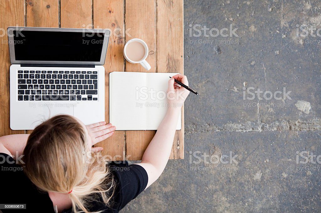 Top view of a woman with laptop and notebook stock photo