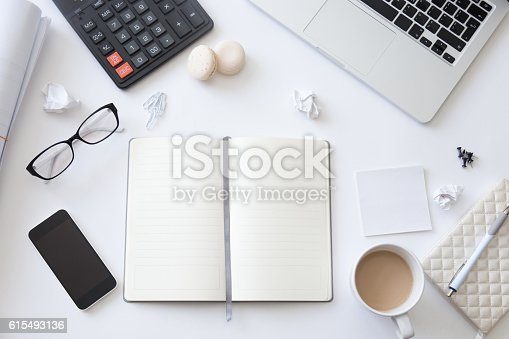 istock Top view of a working desk with open blank notebook 615493136