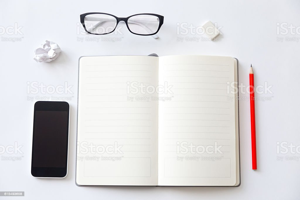 Top view of a working desk with open blank notebook stock photo