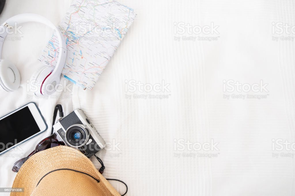 Top view of accessories travel (camera,hat,headphone,map ) on bed blankket.prepareing for holiday vacation trip.journey planning.wanderlust concept with copy space stock photo