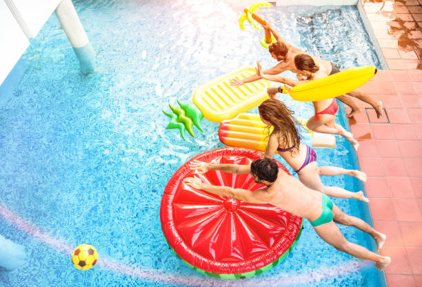 draufsicht der aktiven freunde springen am swimming pool-party - urlaub konzept mit glücklichen jungs und mädchen, die spaß am sommertag im luxusresort - dynamische junge menschen auf warmen hellen sonnenschein filter - kinderparty spiele stock-fotos und bilder