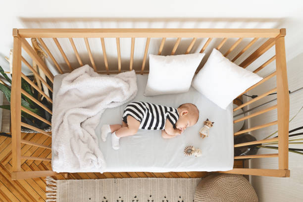 Top view of adorable newborn baby sleeping in wooden crib Sweetest dream. Top view of adorable newborn baby sleeping in wooden crib crib stock pictures, royalty-free photos & images