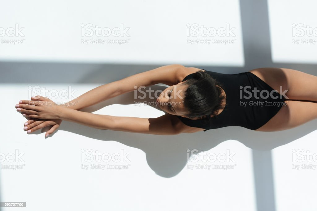 top view of african american stylish sensual woman in black swimsuit relaxing and sunbathing stock photo