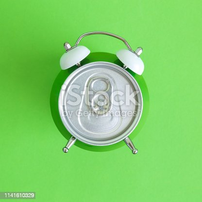 istock Top view of alarm clock drink can isolated on green abstract. 1141610329
