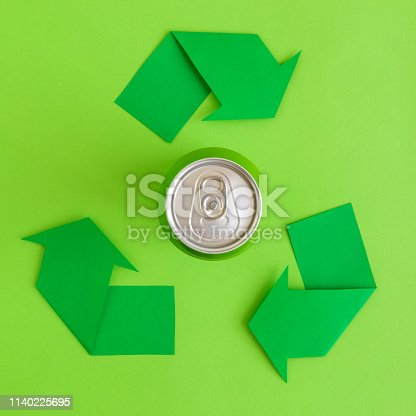 istock Top view of aluminum can and recycling arrows made of paper abstract. 1140225695